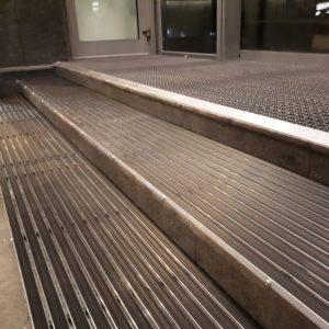 Грязезащитные алюминиевые решетки на ступени в сочетании с модульным покрытием на входе.