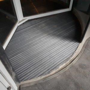 """Придверная алюминиевая решетка под револьверную дверь с укладкой """"под ключ""""."""