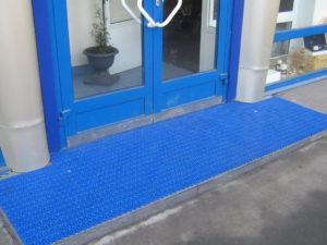 Укладка грязезащитного модульного покрытия синего цвета.