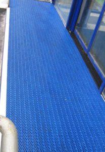 Укладка модульного покрытия синего цвета перед входом.